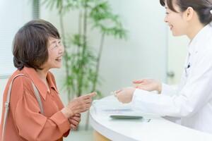 薬局カウンターで会話するシニア女性と女性薬剤師
